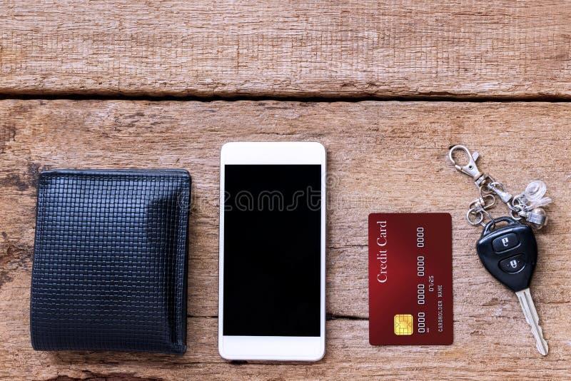 Cartão do telefone celular e de crédito, chave e carteira na tabela de madeira marrom imagem de stock royalty free