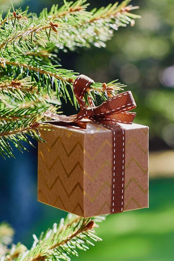 Cartão dos feriados do Natal e do ano novo Caixa de presente que pendura no ramo do abeto no fundo do verde azul fotografia de stock