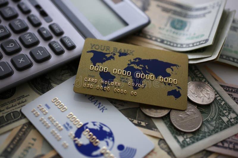 Cart?o e calculadora de cr?dito que encontram-se em uma quantidade grande de dinheiro dos E.U. fotos de stock