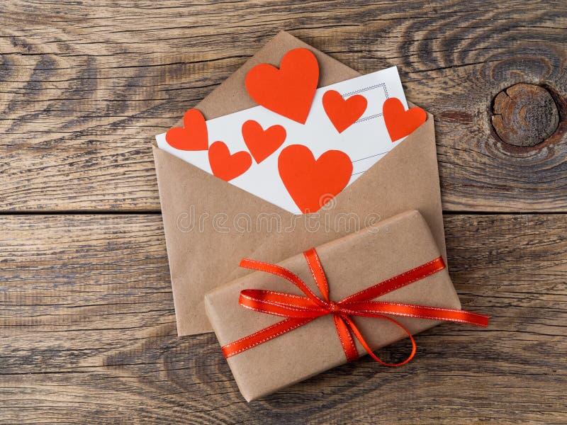 Cartão e corações vermelhos no envelope aberto do papel de embalagem marrom GIF fotografia de stock