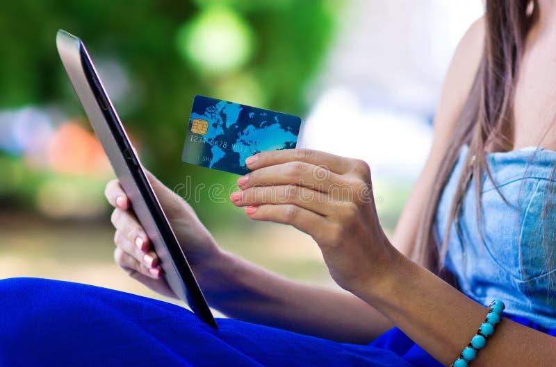 Cartão e tabuleta de crédito da mão da mulher imagem de stock royalty free