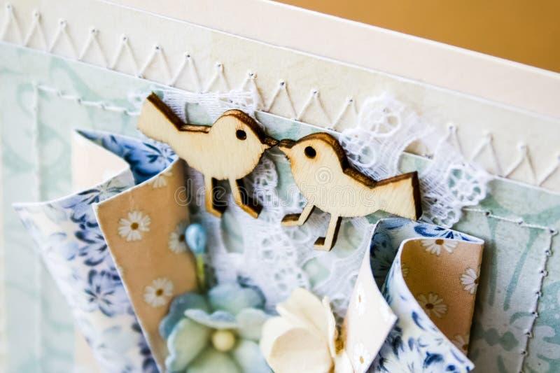 Cartão feito a mão no estilo scrapbooking Dois pássaros de madeira que olham se, laço, mão costurando, flores de papel fotografia de stock royalty free