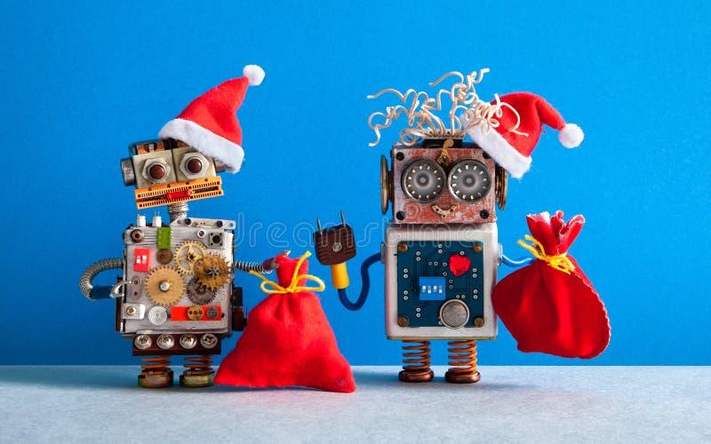 Cartão feliz do ano novo de Chrismas do estilo de Santa Robotic Dois robôs de Santa Claus com sacos de presentes do Xmas Parede a foto de stock royalty free