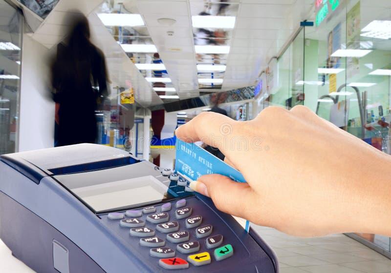 Cartão plástico da terra arrendada humana da mão na máquina do pagamento imagens de stock royalty free