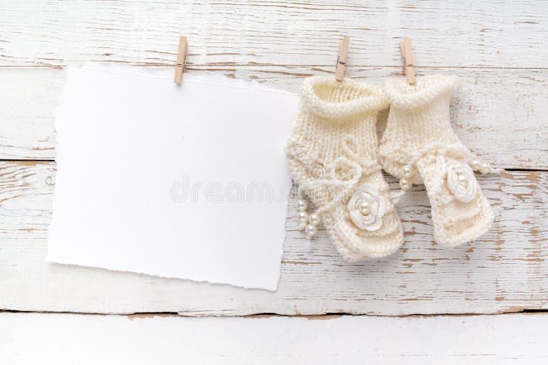 Cartão recém-nascido ou do batismo Placa com as sapatas do bebê no fundo de madeira branco fotos de stock royalty free