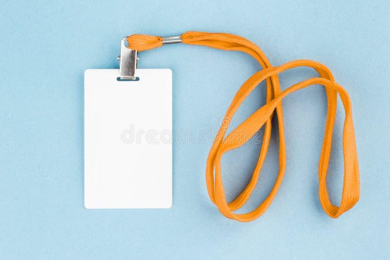 Cartão vazio/ícone da identificação com uma correia alaranjada, em um fundo azul fotos de stock royalty free