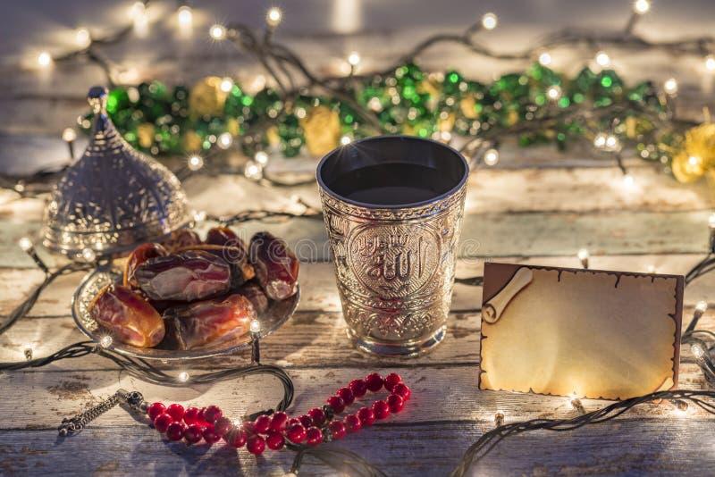 Cartão vazio com datas, rosário, e copo da água com texto de Allah no árabe imagem de stock royalty free