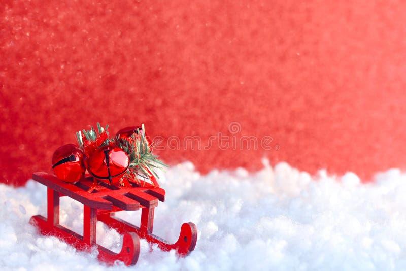 Cartão vermelho do Natal, trenó de madeira do brinquedo, sinos decorativos foto de stock royalty free