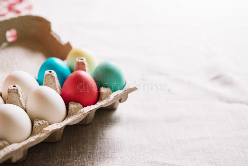 Cartón de huevos con los soportes coloridos de los huevos de Pascua en la lona de lino fotos de archivo