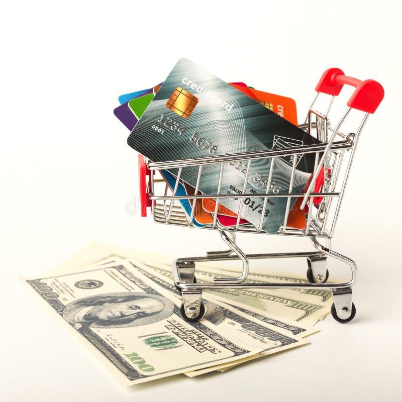 Cartões da cédula e de crédito do dinheiro do dólar do dinheiro no carrinho de compras fotografia de stock royalty free