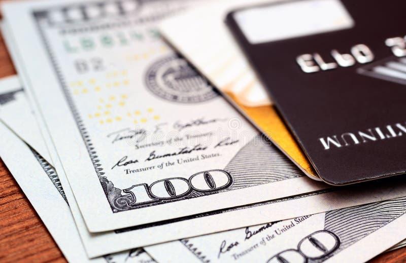 Cartões de crédito do close-up em notas dos dólares com profundidade de campo rasa imagem de stock royalty free