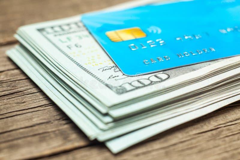 Cartões de crédito e pilha de cédulas 100 dólares no dinheiro Dinheiro eletrônico com uma microplaqueta da segurança para o pagam fotos de stock royalty free