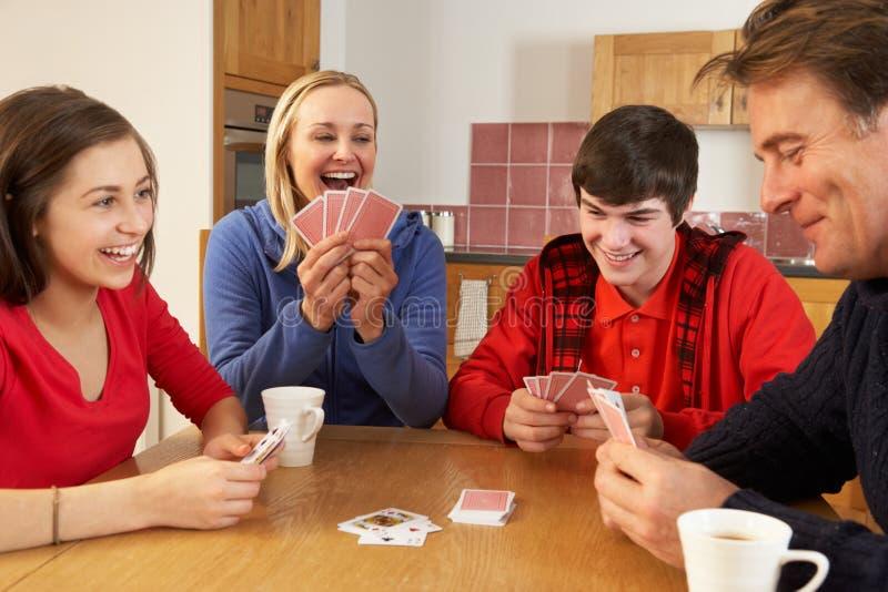 Cartões de jogo da família na cozinha fotografia de stock royalty free