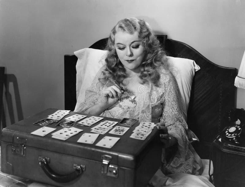 Cartões de jogo da mulher na cama fotografia de stock royalty free