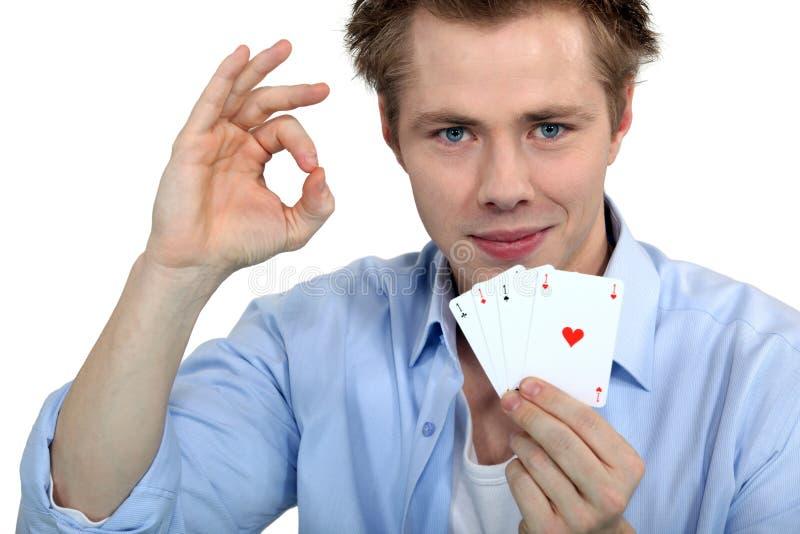 Cartões de jogo da terra arrendada do homem novo fotografia de stock