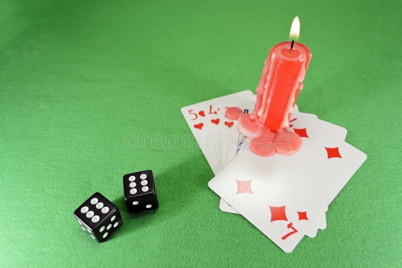 Cartões de jogo, dados e uma vela imagem de stock