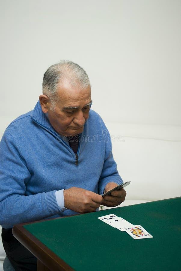 Cartões de jogo do homem sênior foto de stock