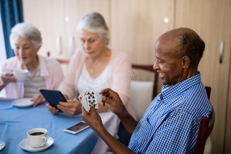 Cartões de jogo do homem superior com amigos ao comer o café imagens de stock royalty free