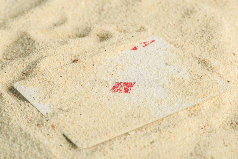 Cartões de jogo do pôquer enterrados em uma duna de areia fotografia de stock royalty free