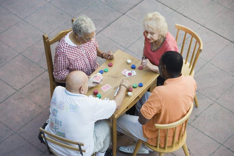 Cartões de jogo multi-étnicos superiores dos amigos junto imagem de stock royalty free