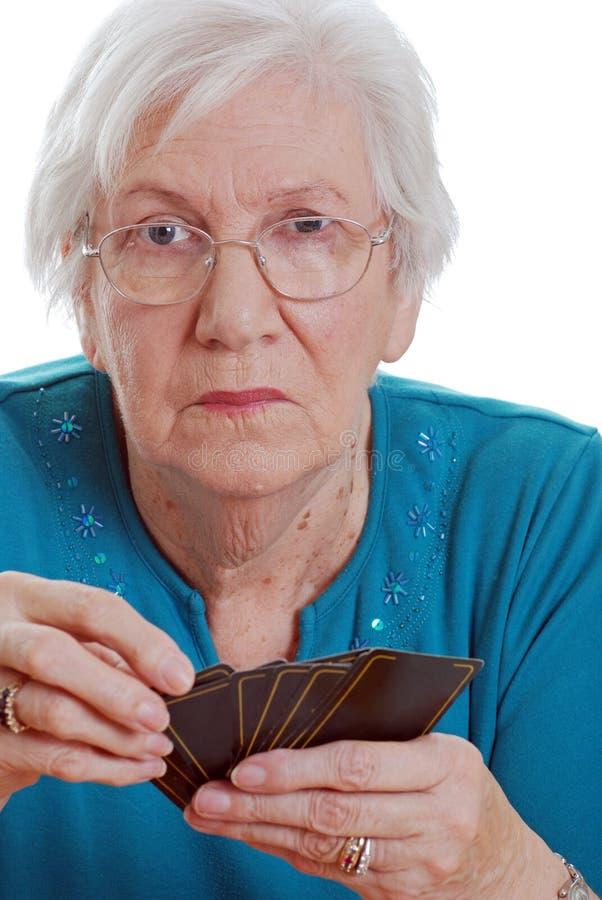 Cartões de jogo sênior da terra arrendada da mulher foto de stock