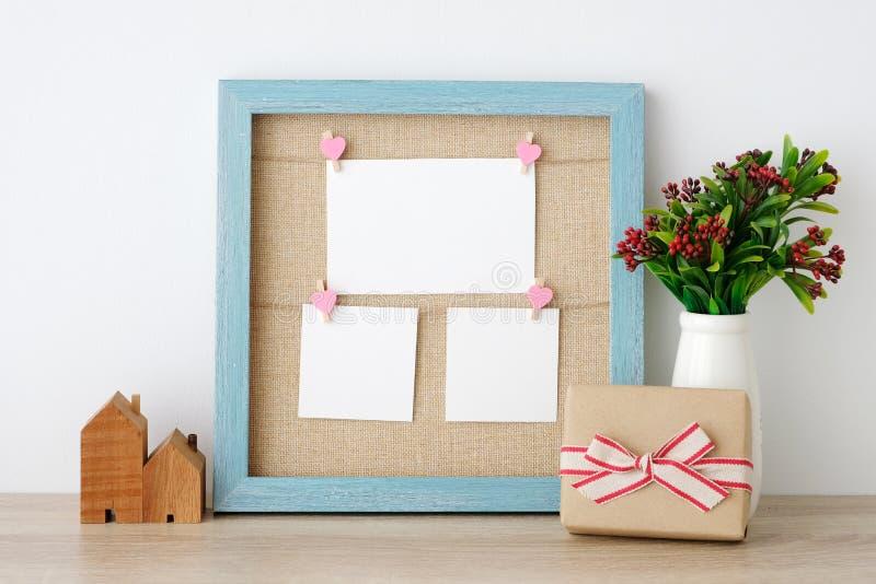 Cartões de papel vazios que penduram no quadro de madeira e no presente do vintage azul fotos de stock royalty free
