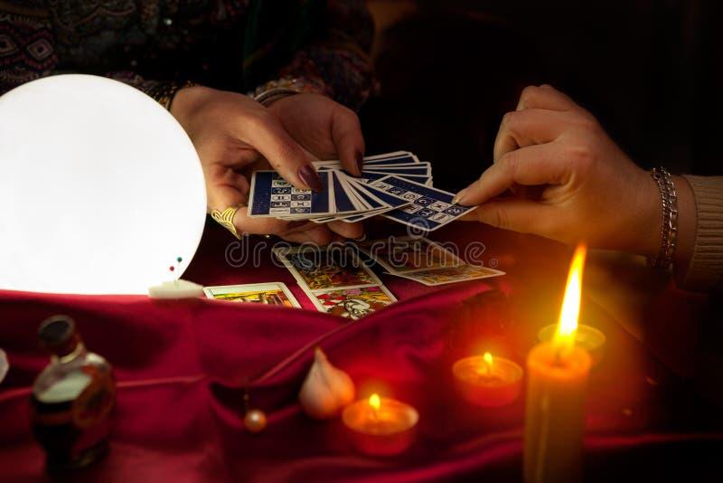 Cartões de tarô nas mãos do caixa de fortuna aciganado velho foto de stock