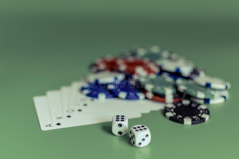 Cartões e dados coloridos de jogo das microplaquetas em um flash verde do fundo real fotos de stock