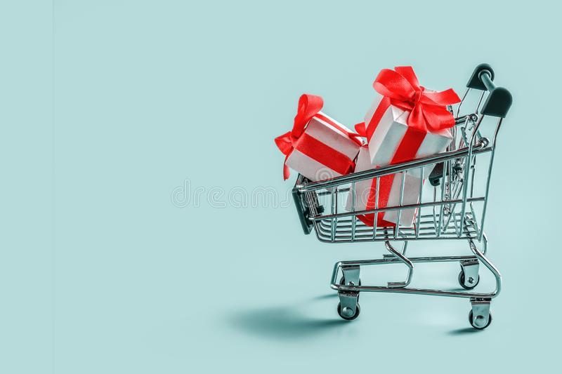 Cart with gift boxes on blue background.  royalty free stock images