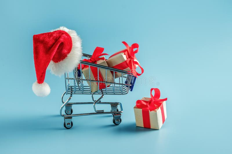 Cart with gift boxes and Santa hat. Blue background with supermarket trolley and boxes with bow stock photos