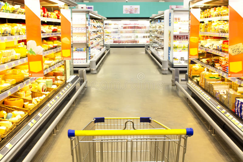Cart at the grocery store. Empty cart at the grocery store. Showcase with cheeses stock photos