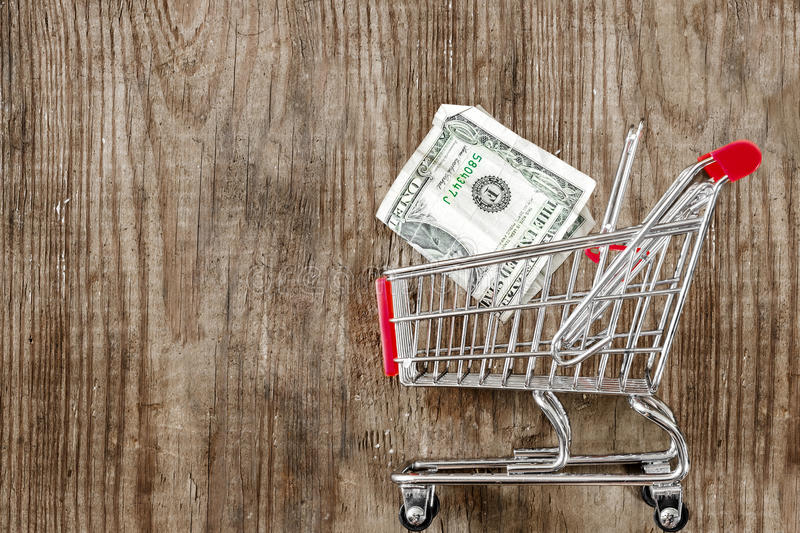 Cart from the grocery store and money on wooden background. Retail trade and advertising. royalty free stock photos