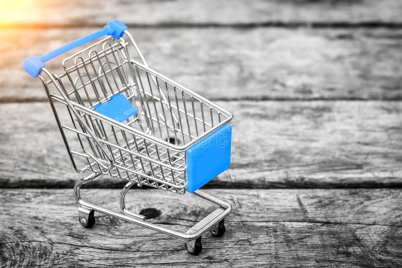 Cart from the grocery store on the old wooden background. Empty shopping trolley. stock photos