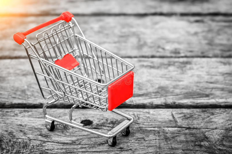 Cart from the grocery store on the old wooden background. Empty shopping trolley. Business ideas and retail trade. stock photos