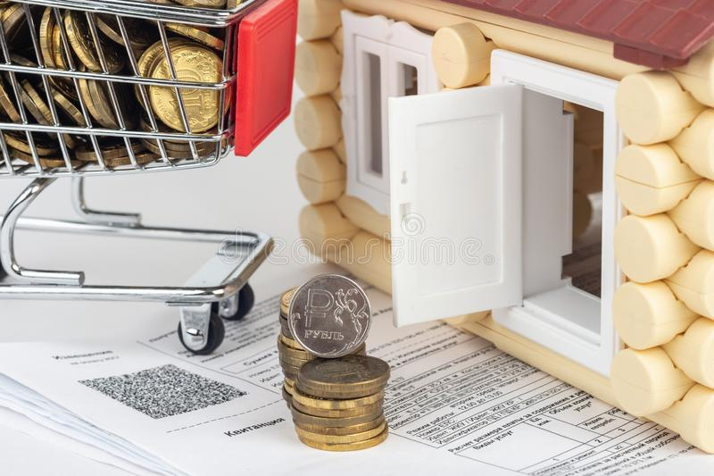 A cart with money, a stack of money and a coin of one ruble in the bills for an apartment, in front of the door to the house stock photography