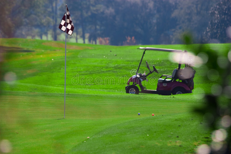Cart near hole on golf course stock photos