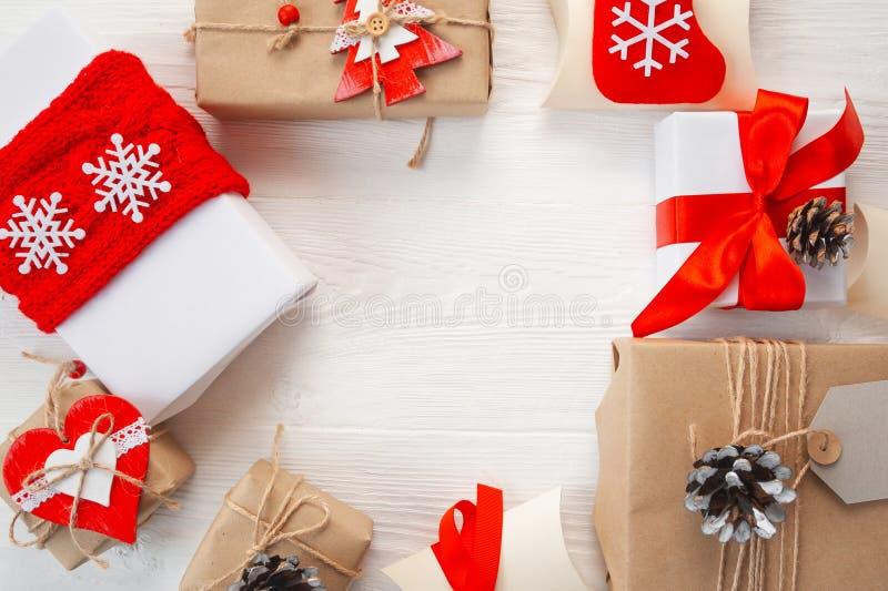 Cart?o de cumprimentos do Natal Branco e caixas de presente de kraft com fita e colisão vermelhas em um fundo de madeira com luga fotos de stock royalty free