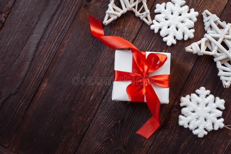 Cart?o de cumprimentos do Natal Caixa de presente branca com fita vermelha e flocos de neve em um fundo de madeira com lugar para fotografia de stock