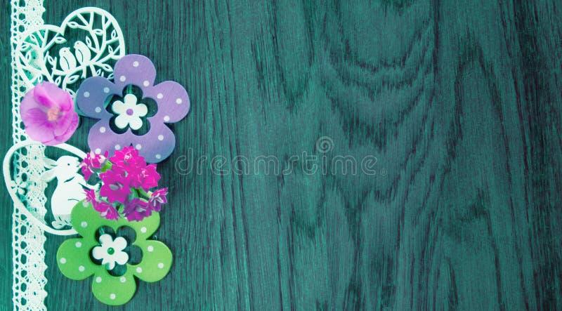 Cart?o de P?scoa, em um fundo da madeira azul com flores e decora??o fotografia de stock