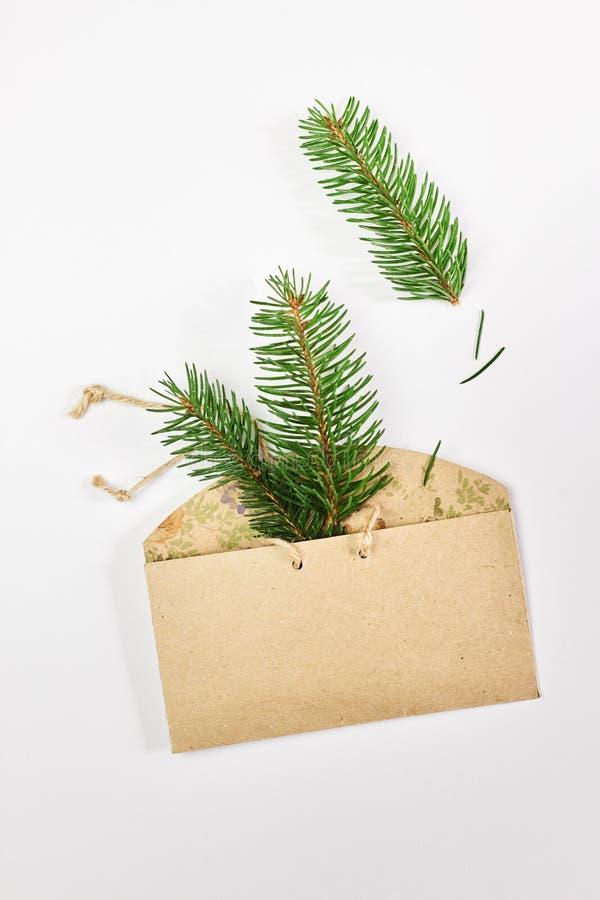 Cart?o do Natal e do ano novo Ramos do abeto no envelope feito a mão do cartão sobre o fundo branco imagens de stock