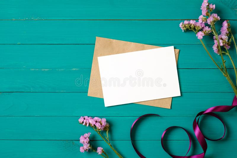 Cart?o e envelope vazios com as flores roxas da margarida na tabela de madeira verde Composi??o colocada lisa, vista superior, em fotos de stock