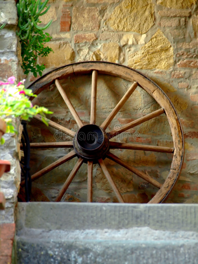 Cart's wheel. A beautiful shot of a cart wheel putted on a stone wall stock photo