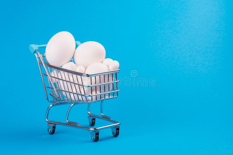 Cart from a supermarket full of eggs. The cart from a supermarket full of eggs on a blue background. Space for text. Preparation for Easter royalty free stock photo