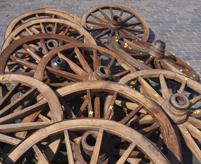 Cart wheels. On the old town square. Cobblestone background stock photo