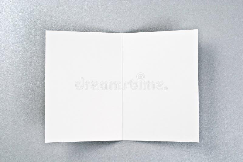 Carta aperta di bianco sopra fondo d'argento immagini stock