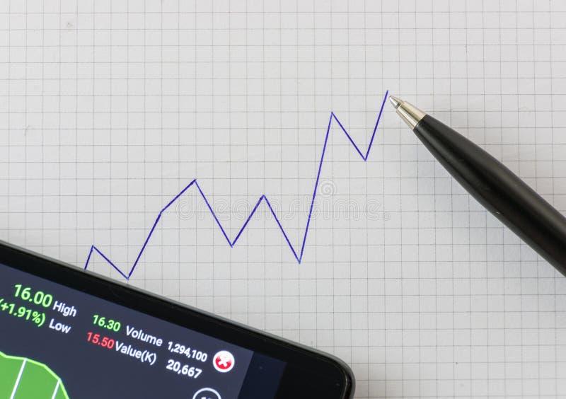 Carta ascendente da tendência da escrita no papel de gráfico com pena preta e no smartphone que abre a aplicação em linha da comp fotos de stock