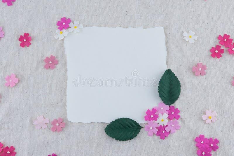 Carta bianca in bianco decorata con i fiori di carta di tono rosa fotografia stock libera da diritti