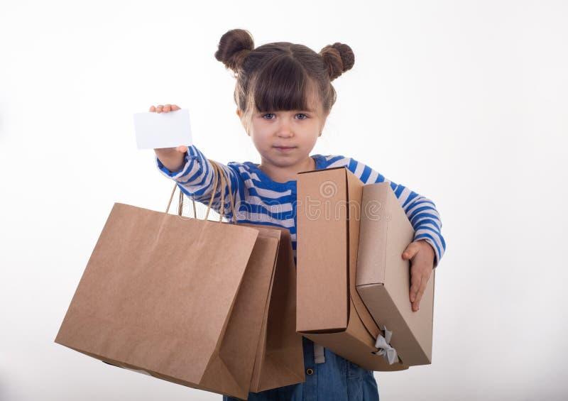 Carta bianca e sacchetti della spesa della ragazza di sconto felice della tenuta in sue mani Bambino con la carta di credito fotografie stock