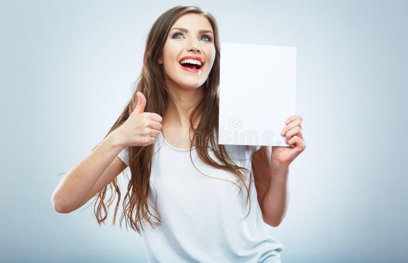 Carta in bianco bianca della tenuta della ragazza dell'adolescente. Pollice su. Giovane wo sorridente immagine stock