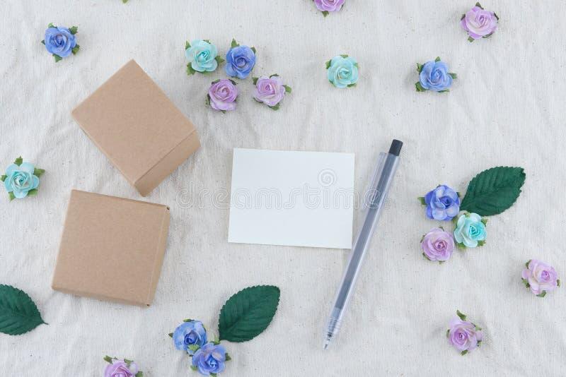 Carta in bianco bianca, penna e contenitore di regalo marrone fotografia stock
